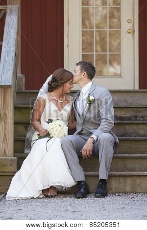 Young newly married couple seated on steps, groom kissing bride on forehead