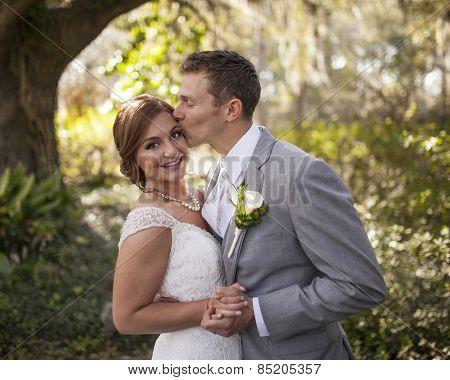 beautiful married couple in garden, groom kissing bride