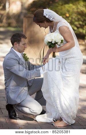 groom helping bride with her wedding dress