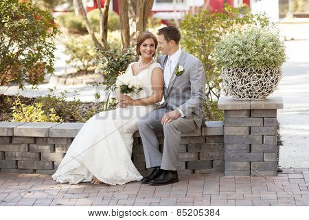 Bride and groom seated in the garden