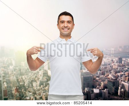 happiness, advertisement, fashion, gesture and people concept - smiling man in t-shirt pointing fingers on himself over city background