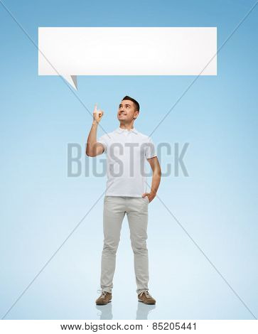 happiness, gesture and people concept - smiling man pointing finger up to white blank text bubble over blue background