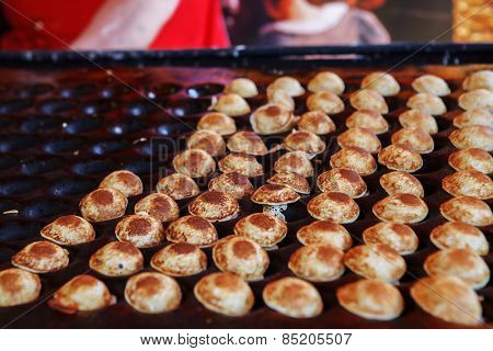 Typical Dutch poffertjes - tiny pancakes-being baked on a heavy cast iron pan