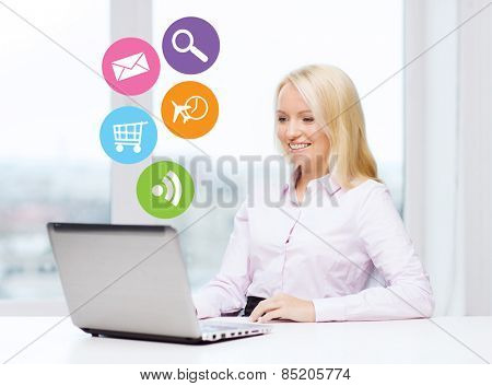 business, people and technology concept - smiling businesswoman or secretary with laptop computer and internet icons in office