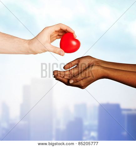 love, charity, valentines day, donation and international concept - close up of man hand giving heart to woman over city background