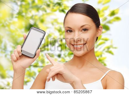 people, technology, communication and internet connection concept - happy young woman pointing finger to smartphone blank screen over green tree leaves background