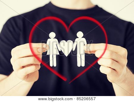 family and relationships concept - man hands showing two paper men with heart shape