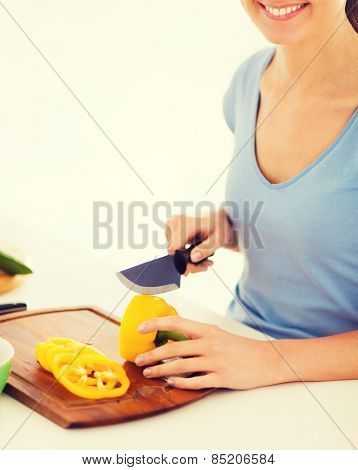 healthy food and kitchen concept - woman hands cutting vegetables