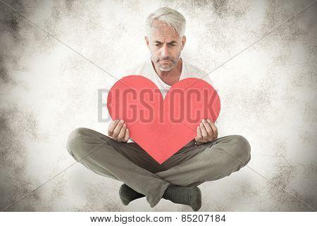 Upset man sitting holding heart shape against grey background