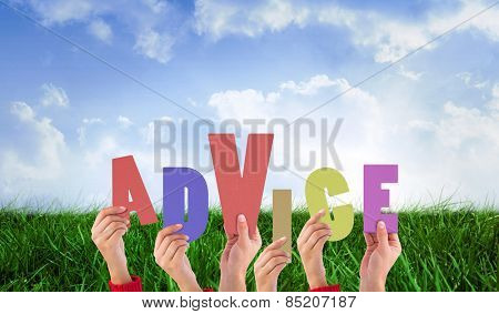 Hands holding up advice against field of grass under blue sky