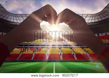 Woman making heart shape with hands against stadium full of spain football fans