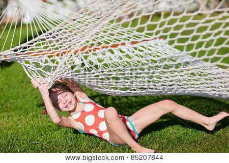 Adorable little girl laughing after falling dawn on a grass from hammock
