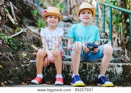Brother and sister outdoor in a park or forest on summer day