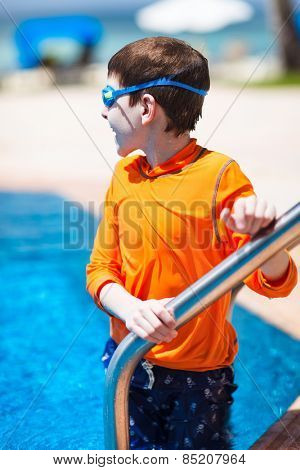 Cute boy wearing sun protection swimwear at pool