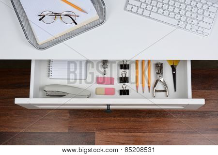 High angle shot of an open desk drawer showing the items inside. The top of the desk has a computer keyboard and wire in-box with paper and pencil. The drawer has pencils, erasers, stapler and more.