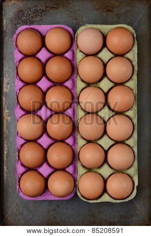 High angle shot of two one dozen cartons of organic brown eggs on a well used cooking surface.. Vertical format.