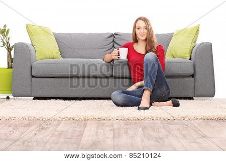 Woman drinking coffee seated by a modern sofa isolated on white background