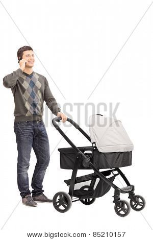 Full length portrait of a young father talking on phone and pushing a baby stroller isolated on white background