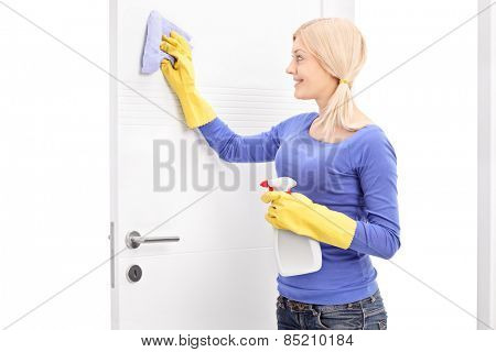 Young woman cleaning a door with a cloth isolated on white background