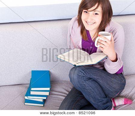 Girl Reading A Book On Sofa
