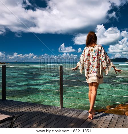 Woman with sarong on a tropical beach jetty at at Seychelles, La Digue.