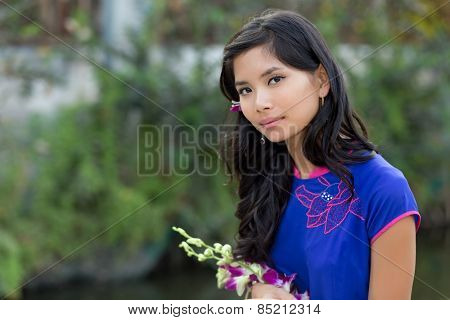Young Vietnamese woman in blue Ao Dai holding flowers while Looking at the Camera.