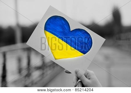 Hands holding paper heart with painted Ukraine flag