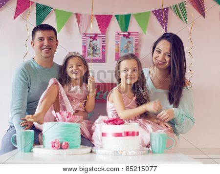 Family celebrating birthday princess party of two 6 years old children