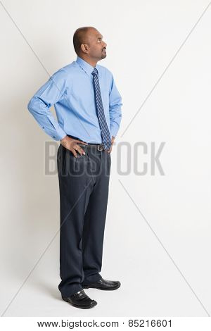 Full body Indian businessman hand on waist looking up at blank copy space, standing on plain background with shadow.