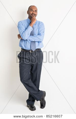 Full body Indian businessman hand on chin and looking up having a thought, standing on plain background with shadow