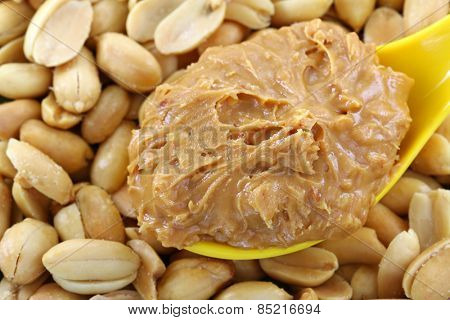 A spoon of creamy crunchy peanut butter on roasted nuts