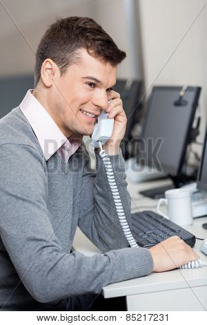 Smiling male customer service representative using landline phone at desk in office