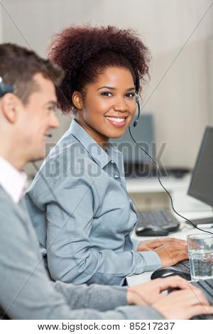 Portrait of beautiful young employee with male colleague working in call center