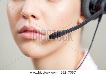 Closeup of female customer service representative wearing headset in office