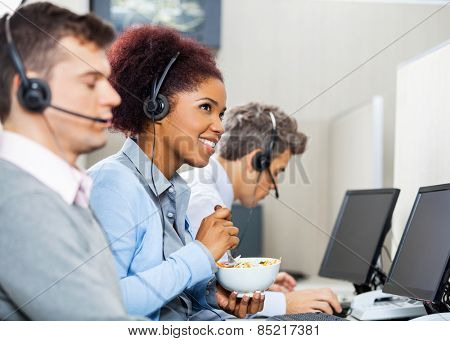 Smiling young female customer service representative having food while colleagues working in office