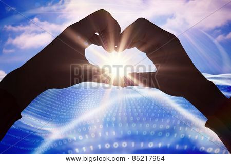 Woman making heart shape with hands against digitally generated binary code landscape