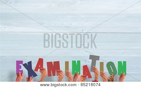 Hands holding up examination against bleached wooden planks background