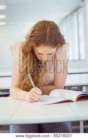 Student taking notes in class at the college
