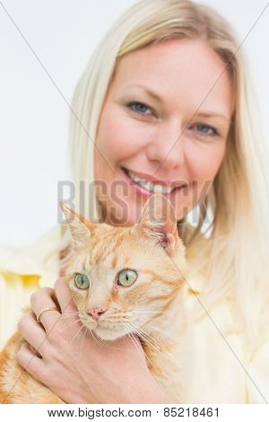 Portrait of happy woman holding cat on white background