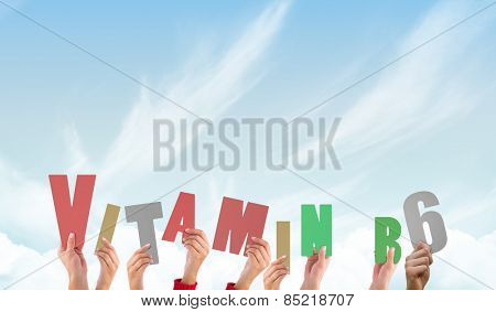 Hands holding up vitamin b6 against blue sky