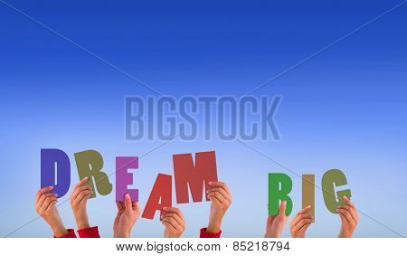 Hands holding up dream big against bright blue sky