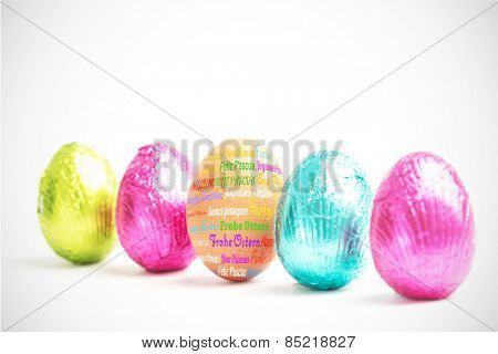 Happy easter in different languages against four easter eggs in a row with one real egg