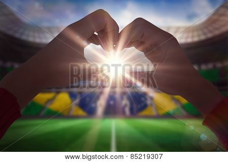 Woman making heart shape with hands against large football stadium with brasilian fans