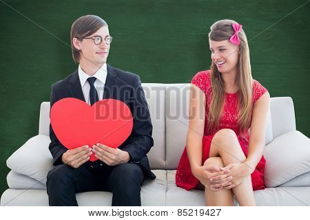 Cute geeky couple with red heart shape against green chalkboard