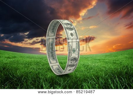 Wheel of dollars against green field under orange sky