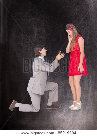 Hipster on bended knee doing a marriage proposal to his girlfriend against black background