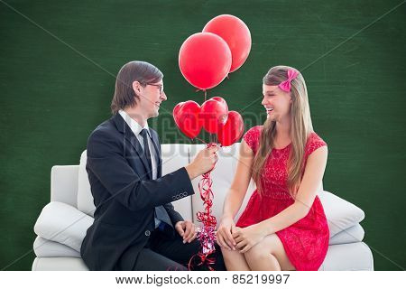 Cute geeky couple with red balloons against green chalkboard