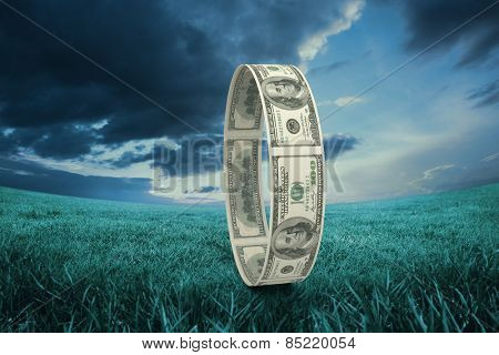 Wheel of dollars against blue sky over green field