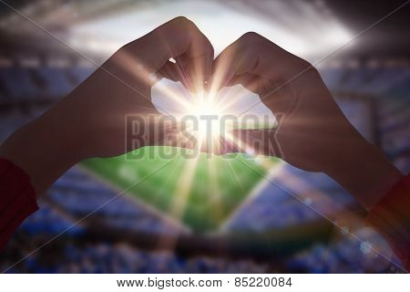 Woman making heart shape with hands against large football stadium with fans in blue