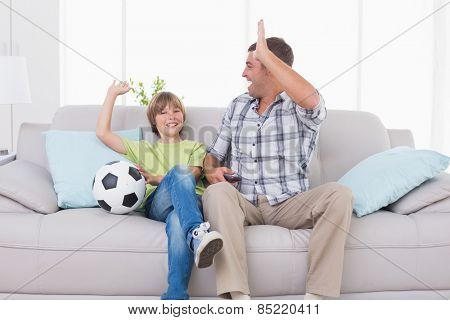 Happy father and son giving high-five while watching soccer match at home